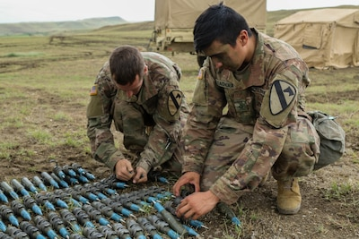 Soldiers prepare artillery rounds.