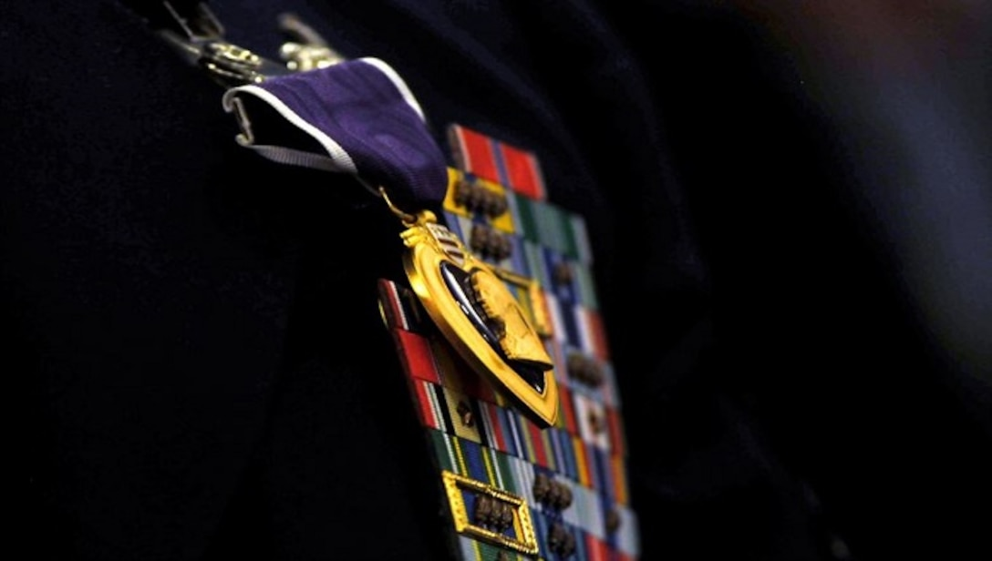 (Former) Chairman of the Joint Chiefs of Staff, Gen. Martin E. Demplsey presents the Purple Heart medal to (then) Tech. Sgt. Richard Chwalik, Dec. 19, 2011 at a town hall meeting during the chairman's visit to Ramstein Air Base, Germany. Chwalik was injured during his deployment to Afghanistan in 2009. (U.S. Air Force photo by Tech. Sgt. Markus M. Maier)