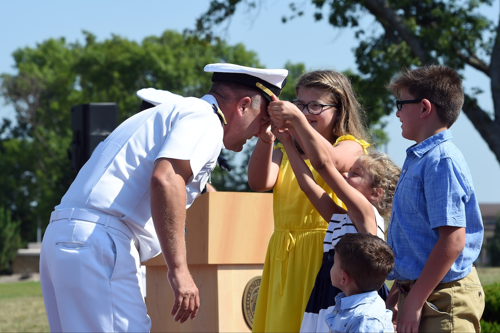U.S. Navy Rear Adm. John Spencer's daughters don his new combination cover with golden oak leaf during his promotion ceremony on the missile deck at U.S. Strategic Command (USSTRATCOM) headquarters on Offutt Air Force Base, Neb., Aug. 9, 2018. Spencer is the executive assistant to U.S. Air Force Gen. John Hyten, commander of USSTRATCOM. His next assignment will be the director of Nuclear Support Directorate, Defense Threat Reduction Agency at Ft. Belvoir, Va.  USSTRATCOM has global responsibilities assigned through the Unified Command Plan that include strategic deterrence, nuclear operations, space operations, joint electromagnetic spectrum operations, global strike, missile defense, and analysis and targeting. (U.S. Navy photo by Mass Communication Specialist 1st Class Julie R. Matyascik/Released)