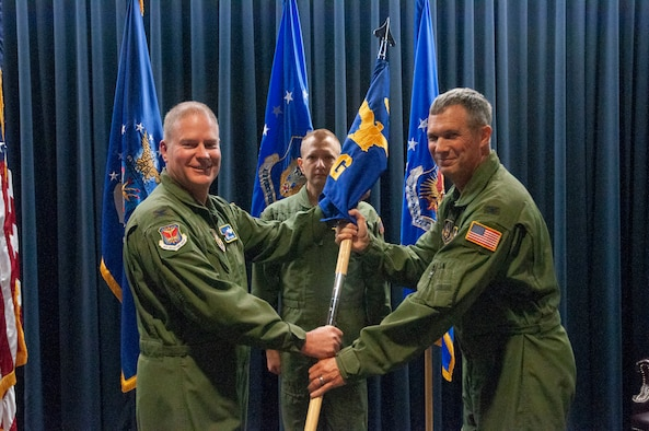 Col. Gregory Berry (right), the new 302nd Operations Group commander, accepts the 302nd OG guidon from Col. James DeVere (left), 302nd Airlift Wing commander, during an assumption of command ceremony at Peterson Air Force Base, Colorado, Aug. 4, 2018