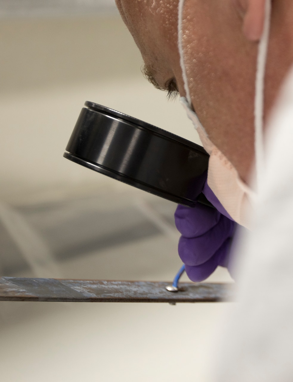 Timothy Kesterson, a latent print examiner, assigned to the Forensic Exploitation Laboratory – Central Command inspects a recovered piece of metal used as a pressure plate in an improvised explosive device uncovered in an undisclosed location in CENTCOM's area of responsibility at Camp Arifjan, Kuwait, August 9, 2018. The FXL-C continually adapts and moves forward with emerging new technology to sustain a powerful and lethal combat force in the battleground.