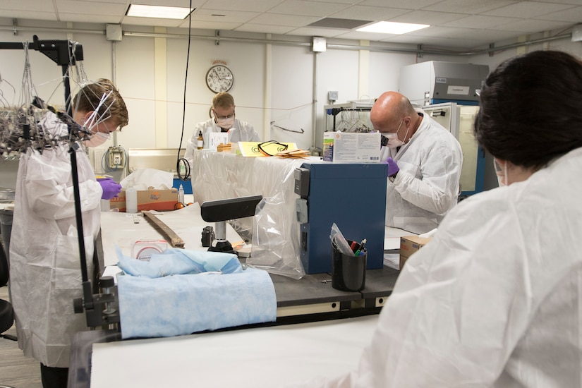 DNA analysts work side-by-side to extract samples from captured enemy material.