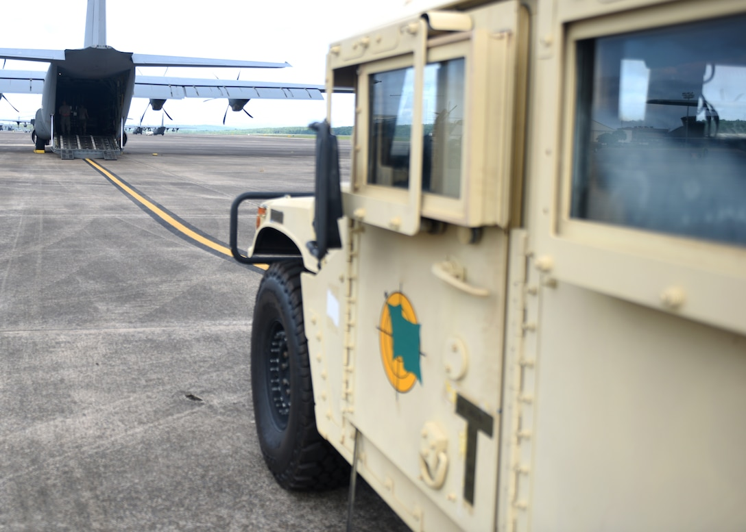 A male in uniform loads a grey C-130J with a vehicle.