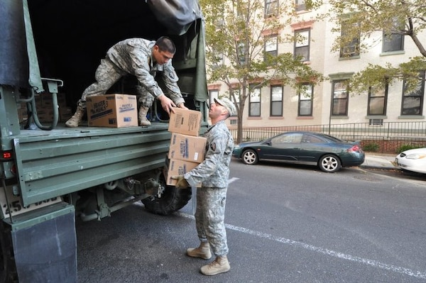 Army Sgt. Joseph Barbado, right, a New Jersey National Guard Soldier, unloads heater meals from a five-ton truck at a distribution point in Hoboken, Nov. 5.