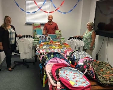 PANAMA CITY, Florida - Members of the Naval Surface Warfare Center Panama City Division (NSWC PCD) Test and Evaluation Prototype Fabrication Division share the assortment of school supplies to be donated. The group worked within their division to collectively provide supplies to children in need. Pictured from left to right: Nicole Waters, Dr. Ben Schlorholtz, and Paula Oliver. U.S. Navy photo by Susan H. Lawson