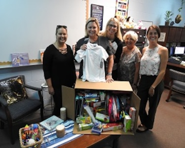 PANAMA CITY, Florida - Deniece Moss (center), principal at West Bay Elementary School poses with employees of Naval Surface Warfare Center Panama City Division's (NSWC PCD) Test and Evaluation Prototype Fabrication Division. The group collected needed school supplies for Bay District School students in Panama City Beach, Florida August 13, 2018. Pictured from left to right: Nicole Waters, Deniece Moss, Michelle Armistead, Paula Oliver, and Halie Cameron. U.S. Navy photo by Susan H. Lawson