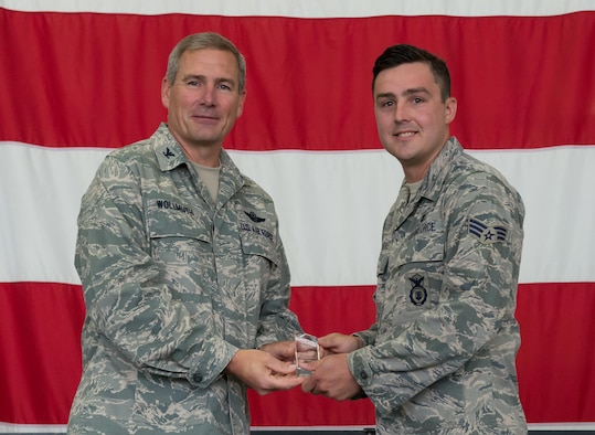 Senior Airman Joel Bakke, 934th Security Forces Squadron, receives the Airman of the Quarter award from Col. Tim Wollmuth, 934th Airlift Wing vice commander, Aug. 5. (Air Force Photo/Tech. Sgt. Amber E.N. Jacobs)