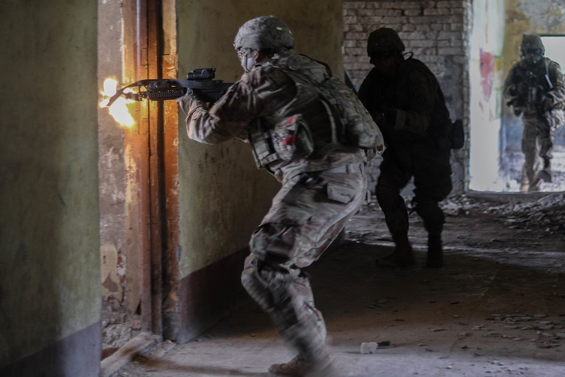 A soldier fires his weapon into a room.