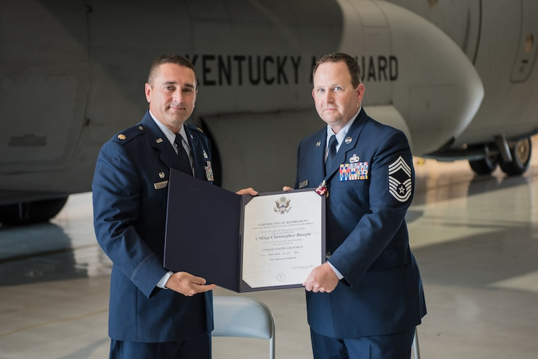 Maj. Jerry Zollman (left), commander of the 123rd Maintenance Squadron, presents the certificate of retirement to Chief Master Sgt. Chris Burgin, superintendent of the 123rd Maintenance Group, during Burgin's retirement ceremony at the Kentucky Air National Guard base in Louisville, Ky., on July 14, 2018. Burgin was the first chief master sergeant selected to fill the newly created superintendent position for the 123rd Maintenance Group. (U.S. Air National Guard photo by Master Sgt. Phil Speck)