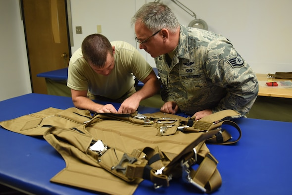 Tech. Sgt. Kurt Mellott and Staff Sgt. Stephen Falker, aircrew flight equipment technicians with the 193rd Special Operations Support Squadron, Middletown, Pennsylvania, Pennsylvania Air National Guard, build a Low-Profile Parachute from scratch Aug. 9, 2018. The new parachutes replaced the old ones, which were originally constructed in the 1980's. (U.S. Air National Guard photo by Senior Airman Julia Sorber/Released)