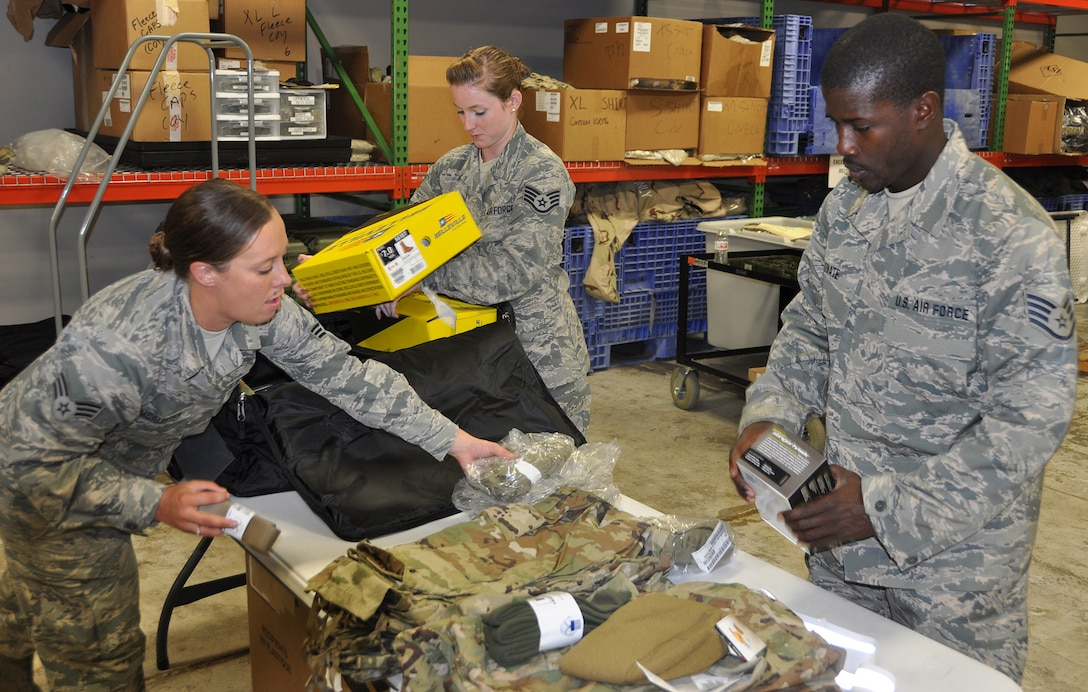 Senior Airman Sarah McAlister and Staff Sgts. Kathryn Fradette and Boubacar Konate, 445th Logistics Readiness Squadron supply technicians, assemble clothing items July 14, 2018