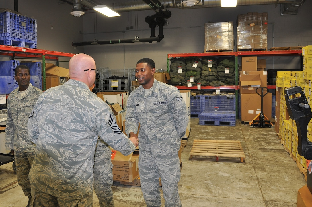 Chief Master Sgt. Paul Stewart, 445th Airlift Wing command chief, coins Senior Airman Gmar Lee, 445th Logistics Readiness Squadron supply technician, July 14, 2018.