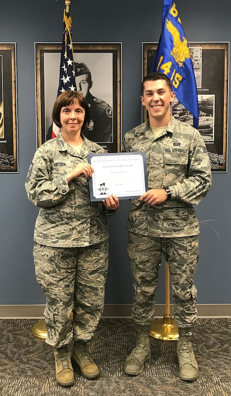 Master Sgt. Angela Hayden, 14th Intelligence Squadron first sergeant, presents the May 2018 Diamond Sharp Award to Senior Airman Alexander Neary, 14 IS operations intelligence journeyman, during the unit training assembly, July 22, 2018.
