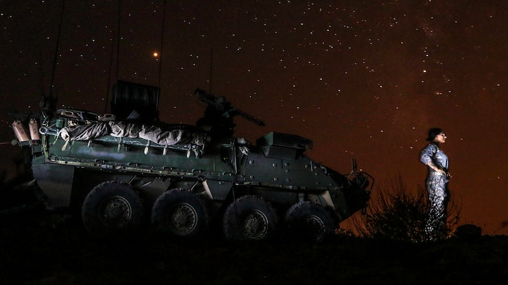A guardsman stands in front of her vehicle and looks at the night sky.