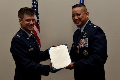 U.S. Air Force Col. Thomas Coakley, 17th Training Group commander, presents a meritorious service certificate to Lt. Col. Abraham Salomon, 17th Training Squadron outgoing commander, during the 17th TRSS Change of Command in the Event Center on Goodfellow Air Force Base, Texas, August 14, 2018. Salomon received the award for his outstanding service to the squadron. (U.S. Air Force photo by Senior Airman Randall Moose/Released)