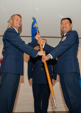 Col. David L. Huang pinned on his new rank, and accepts the 349th Aeromedical Staging Squadron's guidon from Col. John Langell, commander of the 349th Medical Group, during a assumption of command ceremony at Travis Air Force Base, Calif., August 11, 2018.