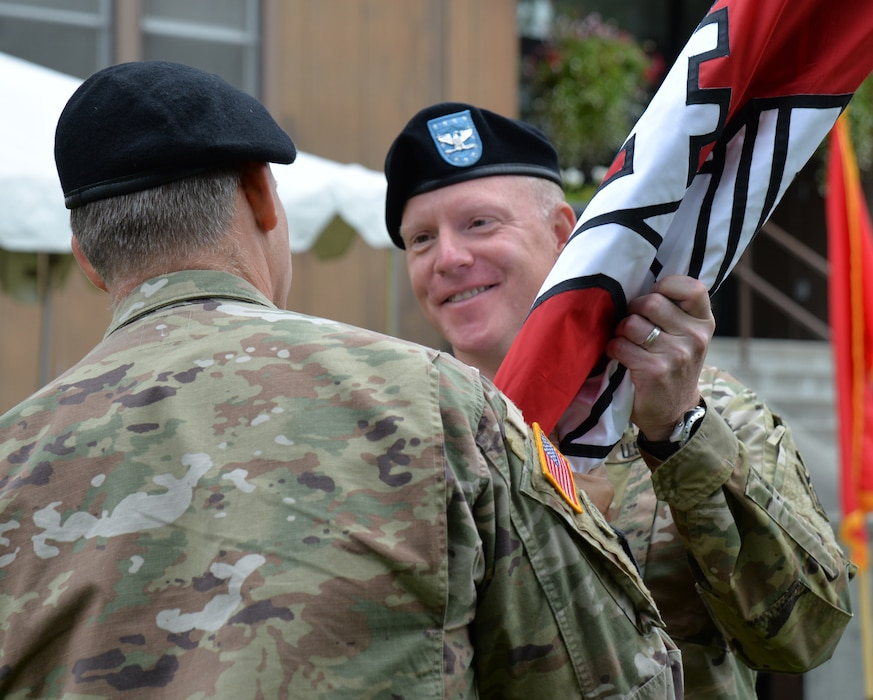 Col. Phillip Borders receives the Corps guidon from Brig. Gen. Thomas Tickner, commanding general of the U.S. Army Corps of Engineers - Pacific Ocean Division, signifying the start of his command of the Alaska District today during a ceremony at the headquarters building on Joint Base Elmendorf-Richardson.