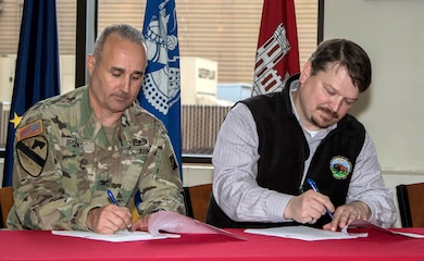 Col. Michael Brooks, commander of the U.S. Army Corps of Engineers - Alaska District, and Joe Balash, U.S. Department of the Interior's Assistant Secretary of Land and Minerals Management, sign the first joint record of decision nationwide Aug.13 between the Corps and the Bureau of Land Management for the Donlin Gold mine project during a signing ceremony at the district headquarters building on Joint Base Elmendorf-Richardson.  Donlin Gold representatives also signed and received the applicable authorizations at the event.