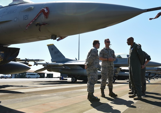 U.S. Air Force Gen. CQ Brown, Jr., Pacific Air Forces commander (right), speaks with Senior Master Sgt. Eric Bennett (middle), 80th Aircraft Maintenance Unit superintendent, and Capt. Donovan Ricks (left), 80th AMU officer in charge, during Exercise Pitch Black 2018, at Royal Australian Air Force Base Darwin, Australia, Aug. 13, 2018. Brown, who started his career at Kunsan Air Base, Republic of Korea, visited with participating Airmen from the 8th Fighter Wing. (U.S. Air Force Photo by Senior Airman Savannah Waters)