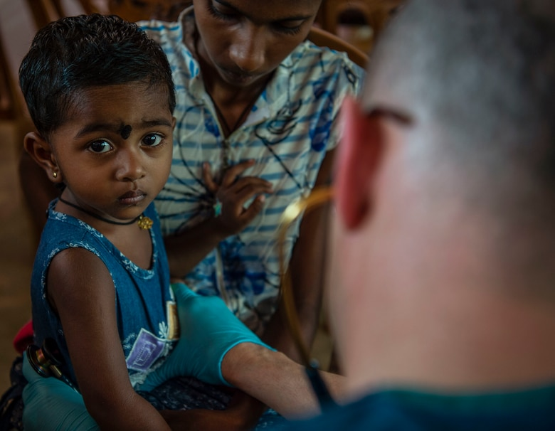 U.S. Air Force Maj. Brad Dayton, 673rd Medical Operations Squadron, Joint Base Elmendorf–Richardson, Alaska, examines a young child during the first day of the Pacific Angel (PAC ANGEL) 18-4 health services outreach event in Vavuniya, Sri Lanka, Aug. 13, 2018.