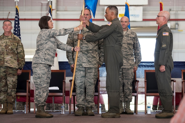West Virginia National Guard Assistant Adjutant General - Air, Brig. Gen. Paige Hunter, ceremoniously hands the 167th Airlift Wing guidon to Col. David Cochran as he assumes command of the wing from Col. Shaun Perkowski, left, during a change of command ceremony, Aug. 5, at the Martinsburg, W.Va. air base. (U.S. Air National Guard photo by Senior Master Sgt. Emily Beightol-Deyerle)