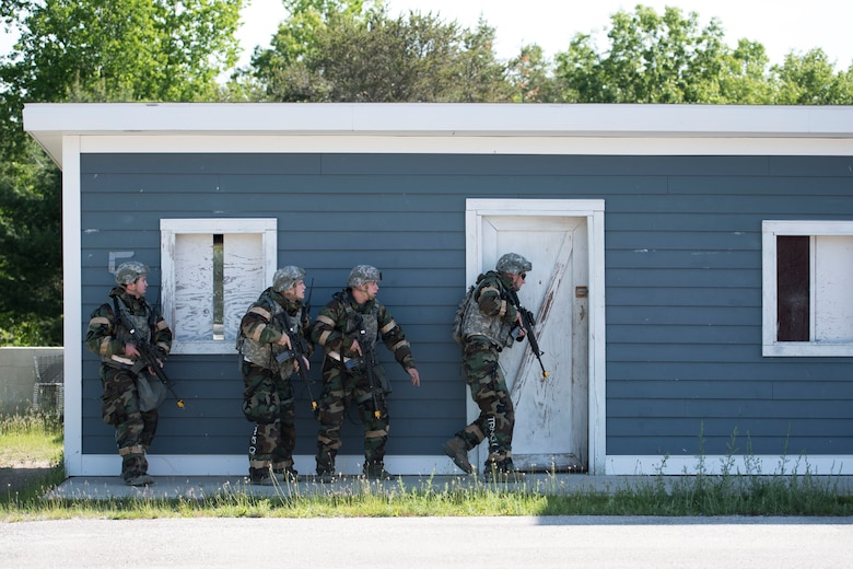 Four Airmen assigned to the 167th Security Forces Squadron prepare to enter a building in a mock village during a deployment training exercise at the Alpena Combat Readiness Training Center in Michigan, June 10-14, 2018. Approximately 200 members of the 167th Airlift Wing participated in the event. (U.S. Air National Guard photo by Tech. Sgt. Jodie Witmer)