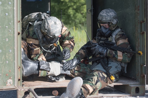 Two Airmen assigned to the 167th Security Forces Squadron use self-aid and buddy care skills to splint a leg during a deployment training exercise at the Alpena Combat Readiness Training Center in Michigan, June 10-14, 2018. Approximately 200 members of the 167th Airlift Wing participated in the event. (U.S. Air National Guard photo by Tech. Sgt. Jodie Witmer)