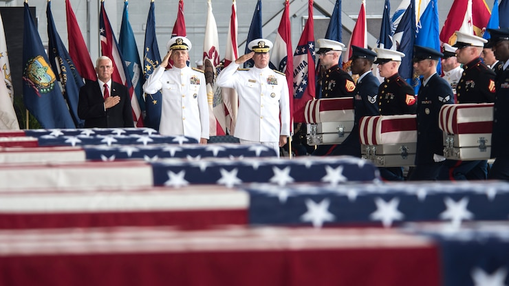 The Vice President and service members render honors with American flag covered coffins.
