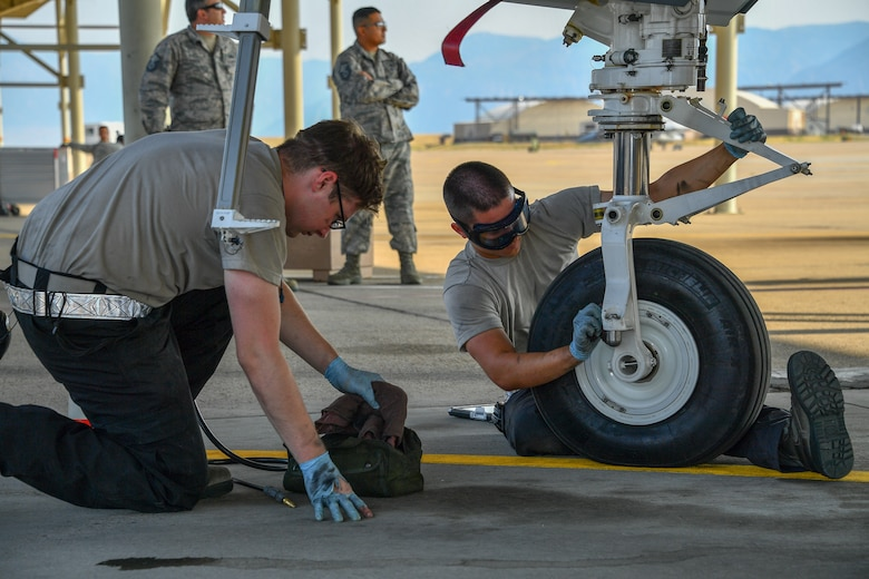 Senior Airman Sergei Ireland, right, and Airman 1st Class James Painter, 421st Aircraft Maintenance Unit crew chiefs, perform maintenance on an F-35A Lightning II fighter jet at Hill Air Force Base, Utah, July 31, 2018. (U.S. Air Force photo by R. Nial Bradshaw)