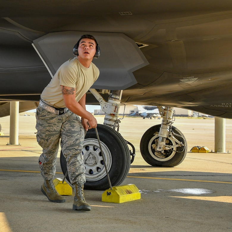 Airman 1st Class Brennan Venable removes chocks from an F35A Lightning II prior to launch at Hill Air Force Base, Utah, July 31, 2018. (U.S. Air Force photo by R. Nial Bradshaw)
