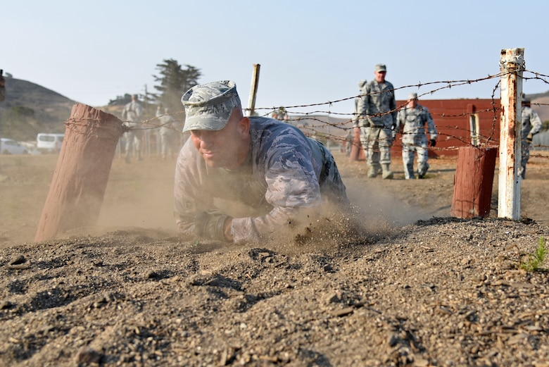 U.S. Air National Guard Chief Master Sgt. Scott Whitley, from the 161st Security Forces Squadron, crawls through a portion of the U.S. Army's confidence course during an annual training event at Camp San Luis Obispo, California, July 31, 2018. The 10-day annual-training exercise brought together Security Forces members from four Air National Guard units in Arizona and Illinois to improve weapons, land navigation, and tactical movement skills. (U.S. Air National Guard photo by Staff Sgt. Dillon Davis)