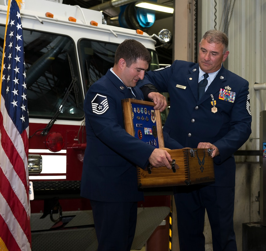 Chief Master Sgt. Anthony M. Lebel, vehicle fleet manager assigned to the 157th Mission Support Group, receives his shadow box from Master Sgt. Christian M. Swegles, a mission generation vehicular equipment mechanic assigned to the 157th MSG,  during a ceremony on Aug. 11, 2018 at Pease Air National Guard Base, N.H. Lebel joined the Air Force  in 1983 and retired after more than 35 years of service. (Photo by Staff Sgt. Kayla White, 157th Air Refueling Wing Public Affairs)