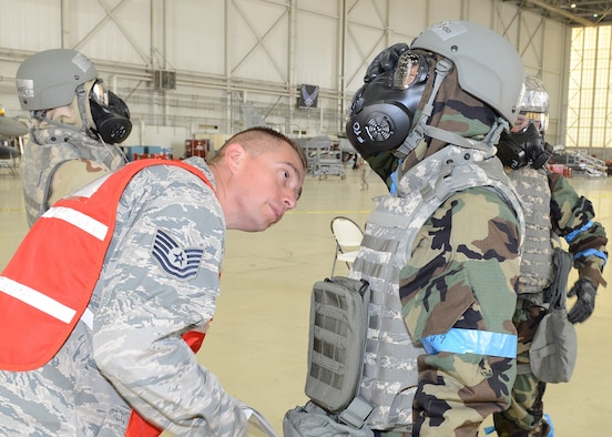 Tech. Sgt. Steven Banda, 412th Maintenance Group, inspects an Airman's protective mask during Test Wing Readiness Exercise 18-03 held in Hangar 1600, Aug. 9. (U.S. Air Force photo by Kenji Thuloweit)