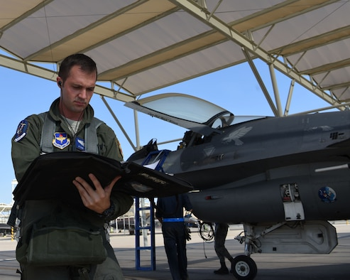 U.S. Air Force Capt. Ryan Neely, 309th Fighter Squadron B flight commander, reviews procedures before inspecting an F-16 Fighting Falcon, Aug. 14, 2018 at Luke Air Force Base, Ariz.