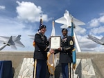 Army Col. Rick Ellis, 8th Theater Sustainment Command deputy commander, present Army Master Sgt. Larry Hogan the certificate of retirement during a ceremony Aug. 14 at Joint Base Pearl Harbor Hickam Missing Man Formation.  Photo by Dr. John Hamilton