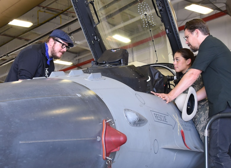 Director and Oscar-nominated actor Ethan Hawke and fellow actor and musician Ben Dickey look inside an F-16 Fighting Falcon while Master Sgt. Michelle Boutell, 301st Maintenance production superintendent, shares details about the jet during their visit to the 301st Fighter Wing, Aug. 15, 2018. The two visited Naval Air Station Fort Worth Joint Reserve Base, Texas to premiere their latest movie, Blaze, for service members and their families. (U.S. Air Force photo by Melissa Harvey)