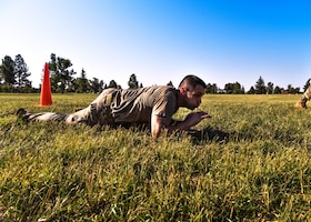 Maj. David Lycan, 890th Missile Security Forces Squadron commander, performs a low crawl as part of the U.S. Marine Corps Combat Fitness Test Aug. 9, 2018 on F.E. Warren Air Forces Base, Wyo. While the Marines have to complete this test along with their annual physical fitness test, the Air Force doesn't have a test in place to simulate battlefield scenarios, taking on the Marine CFT gives Airmen the opportunity to demonstrate their capabilities. (U.S. Air Force photo by Airman 1st Class Braydon Williams)