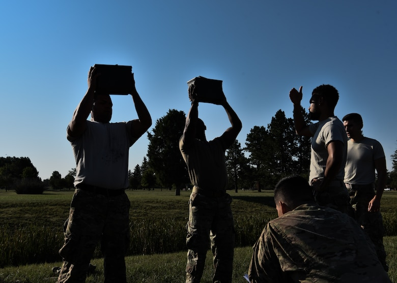 Airman from the 890th Missile Security Forces Squadron lift a 30 pound ammo can above their head as many times as possible in two minutes as part of the U.S. Marine Corps Combat Fitness Test Aug. 9, 2018 on F.E. Warren Air Force Base, Wyo. The CFT is a test designed to simulate combat scenarios while also testing the capabilities of the U.S. military's front line war fighters. (U.S. Air Force photo by Airman 1st Class Braydon Williams)