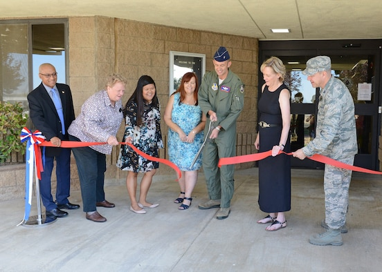 From left to right: Murray Westley, 412th Civil Engineer Squadron director; Gwyneth Bown, 412th Force Support Squadron Child and Youth Programs Flight chief; Colleen Evangelista-Weeks, 412th FSS; Kristen Burks, 412th FSS; Brig. Gen. E. John Teichert; 412th Test Wing commander; Janice Hollen, 412th FSS director; and Col. Jeffry Hollman, 412th Mission Support Group commander; cut the ceremonial red ribbon to officially reopen the School Age Annex Aug. 15. (U.S. Air Force photo by Kenji Thuloweit)