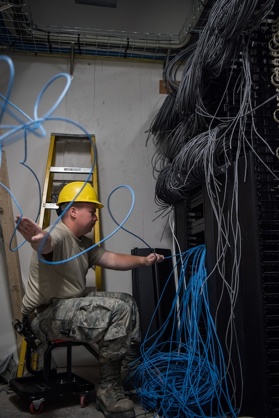 Staff Sgt. Tyler Evans, a 205th Engineering and Installation Squadron (205th EIS) cable installations Airman, feeds cable as he creates a telecommunications connection point in the main distribution frame, where communications from outside the building are routed and connected to internal networks, July 24, 2018, during a hangar renovation project at Buckley Air Force Base in Aurora, Colorado. The 205th EIS team, from Will Rogers Air National Guard Base in Oklahoma City, completed more than 1,000 cable drops and installed an estimated 200,000 feet of indoor cable as part of the 6-week install for the renovation, which was estimated to be a $22 million project in total. (U.S. Air National Guard photo by Staff Sgt. Brigette Waltermire)