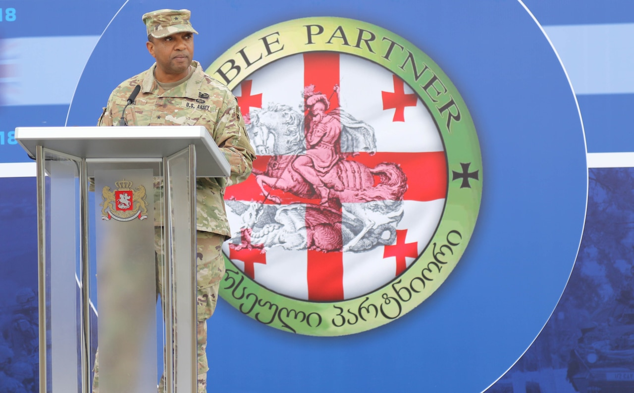 An Army officer speaks at a podium in front of a large red and white logo.