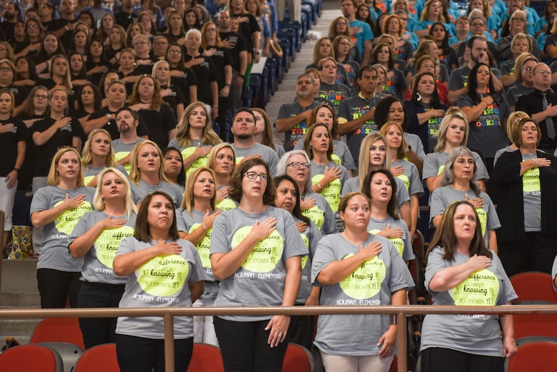 Faculty from Holiman Elementary School stand for the national anthem during the San Angelo Independent School District's annual convocation at the Foster Communications Coliseum, San Angelo, Texas, Aug. 15, 2018. The event signified the kickoff of the 2018 to 2019 school year. (U.S. Air Force photo by Aryn Lockhart/Released)