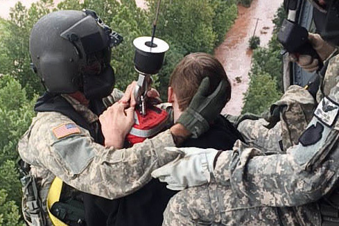 Two soldiers hold onto a child in a helicopter after rescuing him from floodwaters in Pennsylvania.