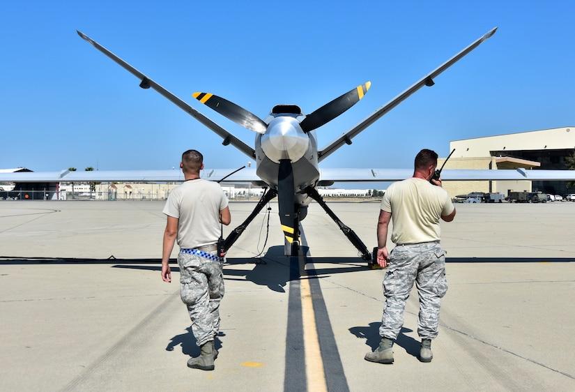 Airmen do a preflight check on a drone.