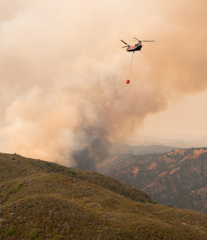 Helicopter approaches to drop water on a wildfire.