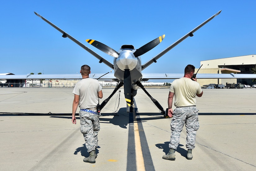 Two airmen inspect a plane.