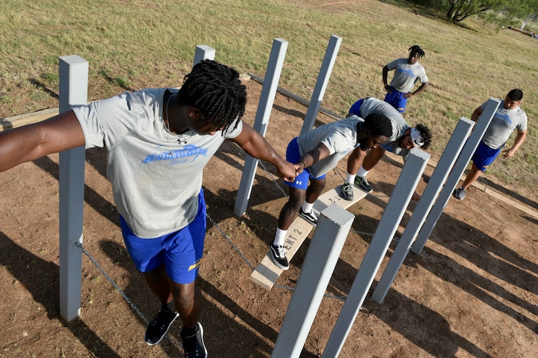 Angelo State University students help each other over a chain bridge on Specker's Ascension obstacle on Goodfellow Air Force Base, Texas, Aug. 15, 2018. The 344th Military Intelligence Battalion dedicated the six obstacles to soldiers who earned the Medal of Honor. (U.S. Air Force photo by Senior Airman Randall Moose/Released)