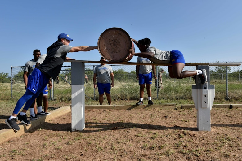 Angelo State University students, Payne Sullins and Bam Howard, move a barrel over the Benavidez's Rescue obstacle on Goodfellow Air Force Base, Texas, Aug, 15, 2018. Each course has three parts, delivering supplies or wounded personnel over difficult terrain and ensuring the safe passage of each team member. (U.S. Air Force photo by Senior Airman Randall Moose/Released)