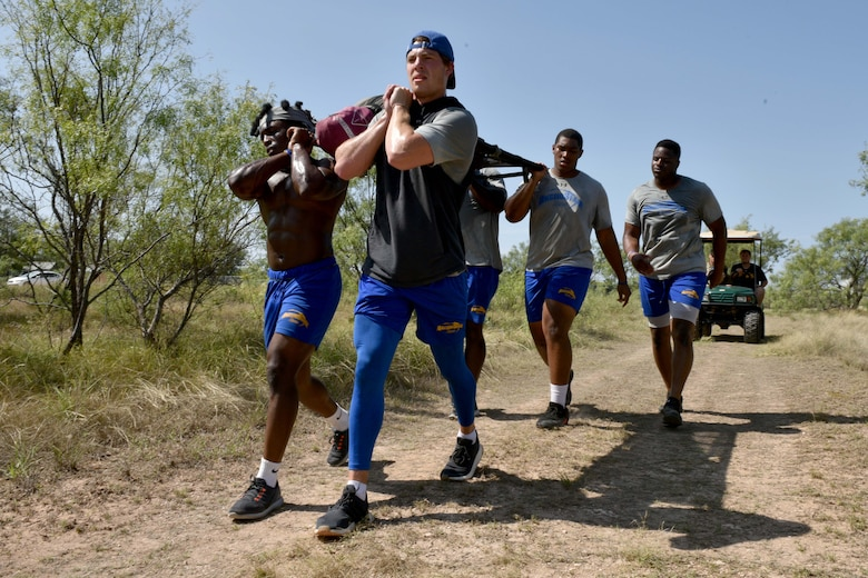 Angelo State University students carry a 200-pound litter and 30 gallons of water over half a mile as fast as possible on Goodfellow Air Force, Texas, Aug, 15, 2018. This exercise tested the student's endurance, adding stress to the experience. (U.S. Air Force photo by Senior Airman Randall Moose/Released)