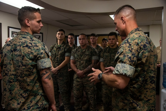 Col. Kyle B. Ellison, commanding officer, 7th Marine Regiment, speaks about the actions and the esprit de corps that Lance Cpl. Dillon Bennett, machine gunner, 3rd Battalion, 7th Regiment, displayed following the presentation of a Purple Heart to Bennett at 7th Marines' Headquarters aboard the Marine Corps Air Ground Combat Center, Twentynine Palms, Calif., July 27, 2018. Bennett received the Purple Heart for wounds sustained while deployed to his area of operations on July 9, 2018. (Marine Corps photo by Lance Cpl. Dave Flores)